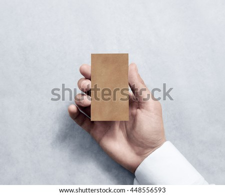 Hand holding blank vertical kraft business card design mockup. Clear calling card mock up template, craft paper. Pasteboard display front. Small offset texture card print. Business identity