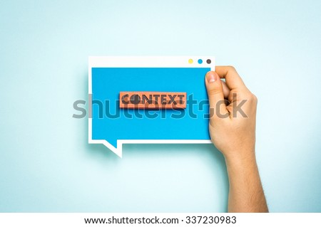 "Hand holding blue speech bubble with the text ""context"". ""Context Marketing"" concept."