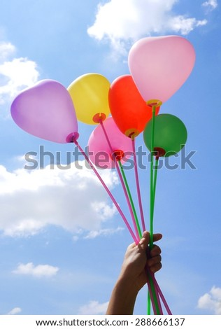 hand holding colorful balloon