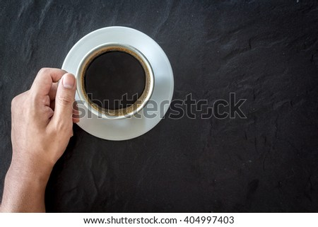 Hand holding cup of coffee  on black background