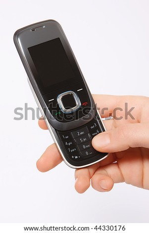 Hand holding grey mobile phone isolated on light grey background