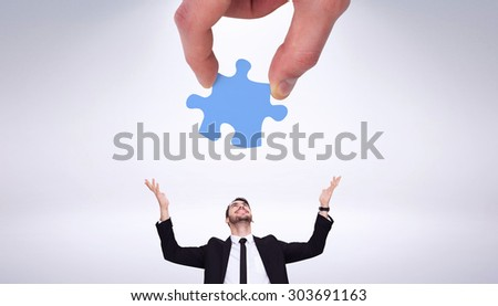 Hand holding jigsaw piece against grey background