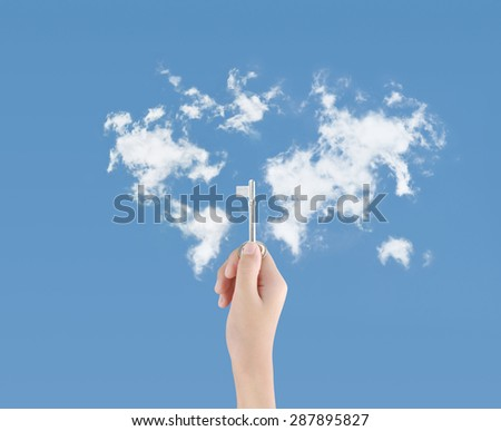 Hand holding key on clouds map background