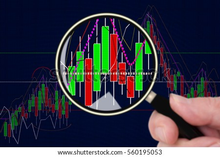 Hand holding magnifying glass in front of chart