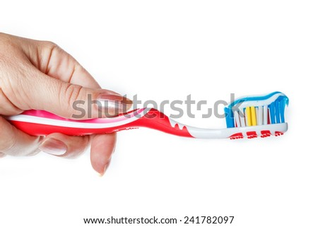 Hand holding red toothbrush with blue two color toothpaste on light surface. Photo of dental hygiene and health maintenance. Object isolated on white background without shadows