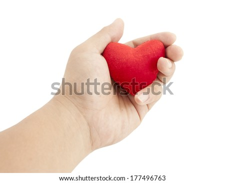 Hand holding small heart shaped pillow isolated on white