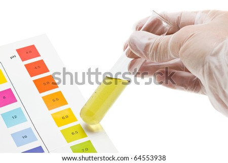 Hand holding test tube with pH indicator comparing color to scale