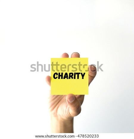 Hand holding yellow sticky note written CHARITY word