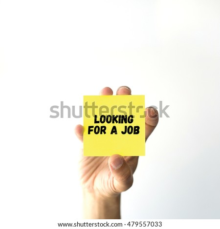 Hand holding yellow sticky note written LOOKING FOR A JOB