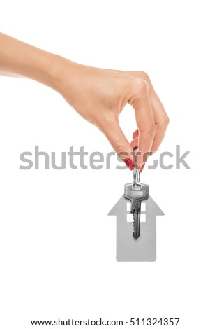 Hand holds key with a keychain in the shape of a house on a white background.