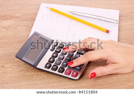 hand, notepad and calculator on wooden background