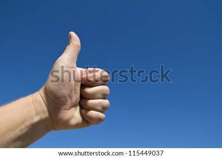 Hand of a man with a thumbs up gesture against a blue sky