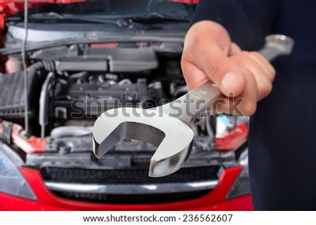 Hand of car mechanic with wrench. Auto repair service