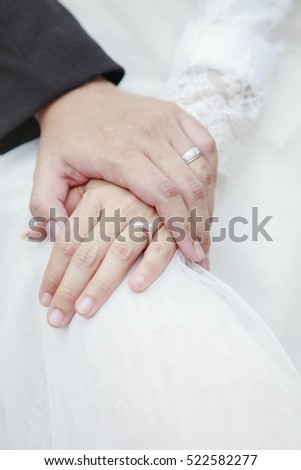 hand of groom and bride warming holding with wedding diamond ring