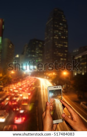 Hand of photographer with smart phone shooting image on blurred traffic jam in Bangkok at night background.