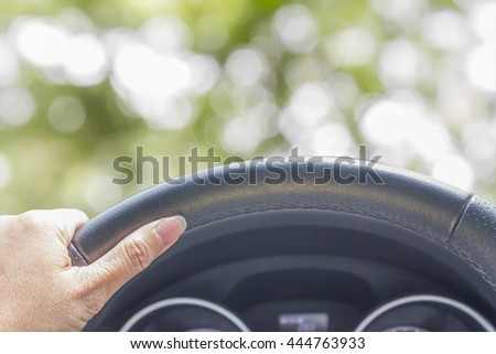 hand of woman driving car on abstract nature bokeh blur background