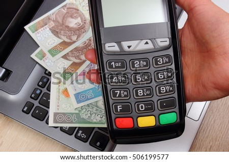 Hand of woman using payment terminal, enter personal identification number, credit card reader, polish currency money on laptop, finance and banking concept
