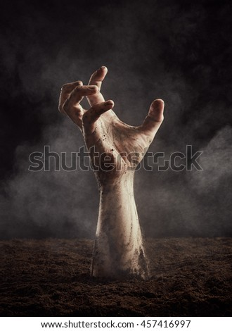 Hand of zombie in dirt climbs out of the ground