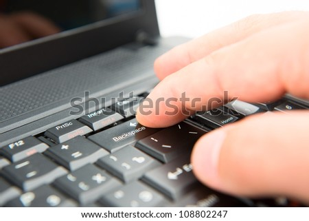 Hand on keyboard pushes button backspase