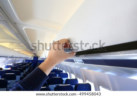 Hand opening white  luggage panel in empty airplane