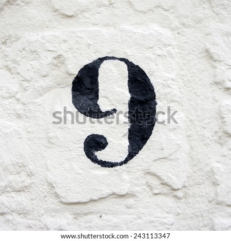 hand painted house number nine. black numeral on a white stucco wall