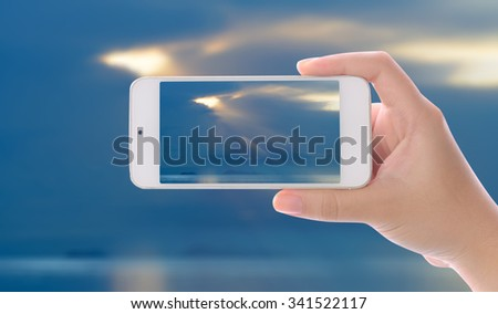 Hand photographed beautiful inspiration sea sunrise by using smartphone
