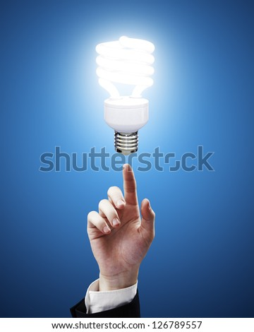 hand pointing to energy saving lamp on blue background