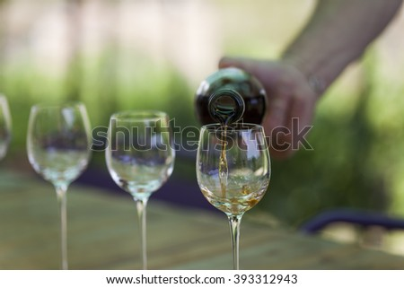 Hand pouring liquor into glasses during a vineyard tour