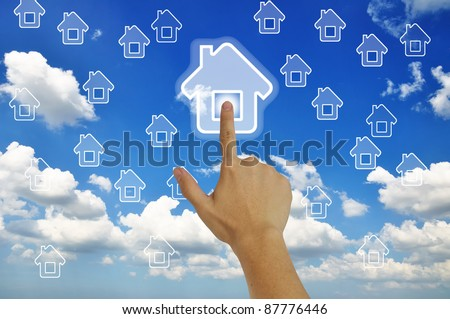 Hand pressing home symbol  on  grassland  blue sky