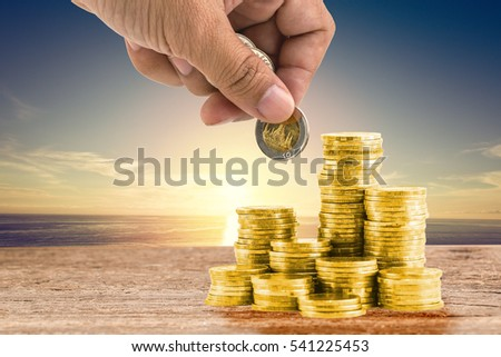 Hand pun money coins on sunset sky background. Invest more concept