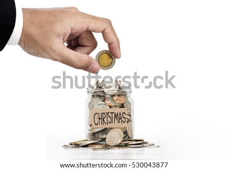 Hand put coin in glass jar, saving money for Christmas, on white background