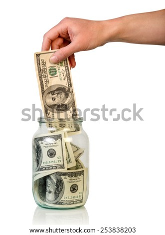 Hand puts money in jar on white background