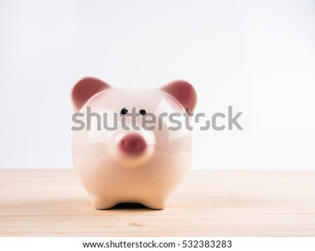 hand putting a coin into a pink piggy bank in saving money for future concept