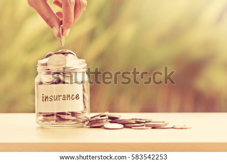 Hand putting Coins in glass jar for money saving insurance concept , vintage color tone