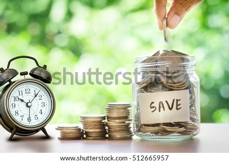 Hand putting Coins in glass jar , time for  money saving financial concept