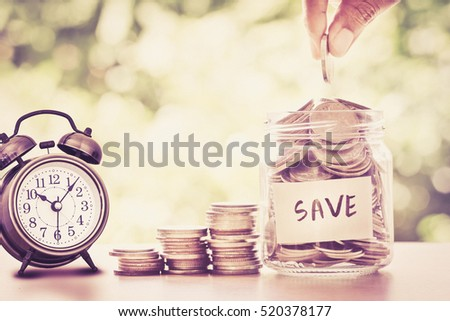 Hand putting Coins in glass jar , time for  money saving financial concept , vintage retro color tone