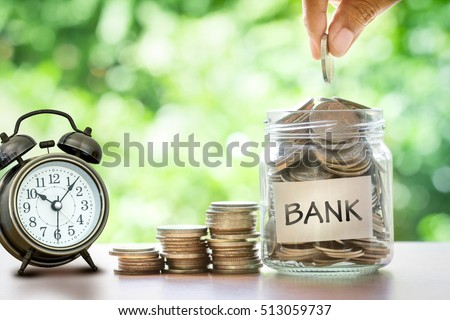 Hand putting Coins in glass jar with alarm clock and bank word . Time to Save money with bank and financial concept