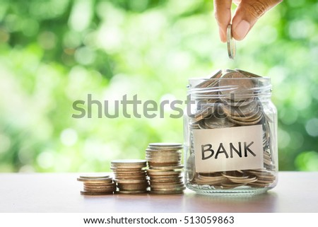 Hand putting Coins in glass jar with bank word . Time to Save money with bank and financial concept