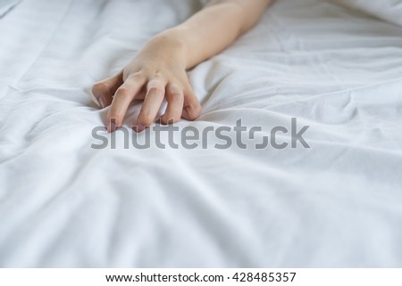 Hand sign orgasm of woman on white bed in hotel