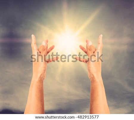 Hand trying to reach on the sky with sun rays, vintage tone