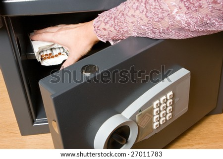 Hand trying to take cigarettes out of the safe