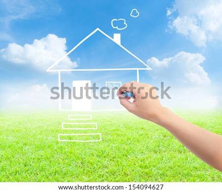Hand with a chalk draws a house on grass with sky.