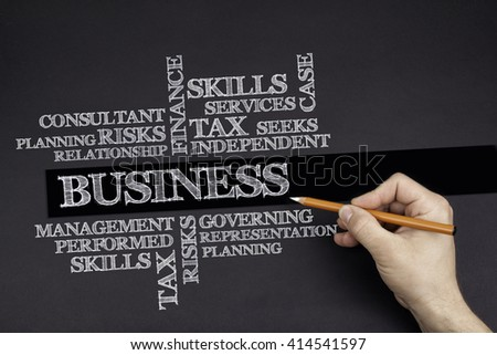 Hand with a white pencil writing: Business word cloud