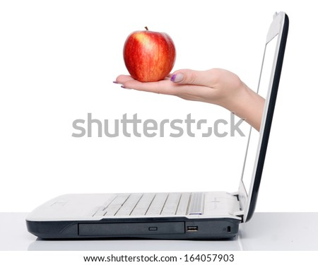 hand with apple comes frome laptop screen isolated on white