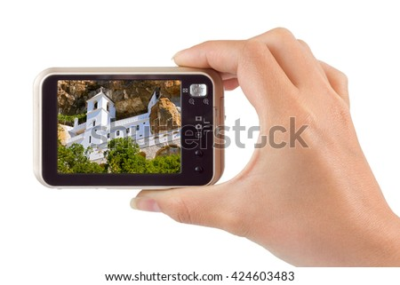 Hand with camera and Ostrog monastery - Montenegro image (my photo) isolated on white background
