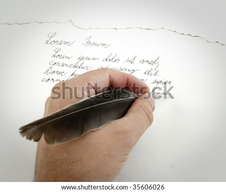 Hand with feather writes letter