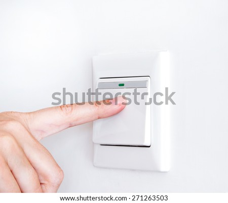 Hand with finger on light switch