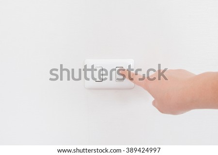 hand with finger on light switch to turn off the lights