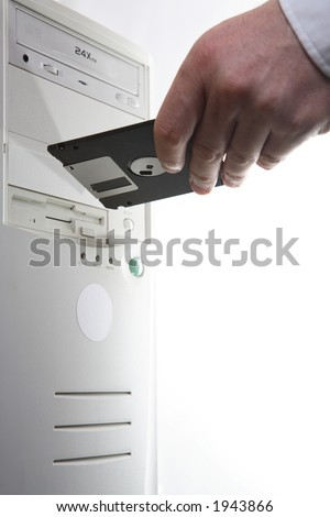 Hand with floppy disc at a computer