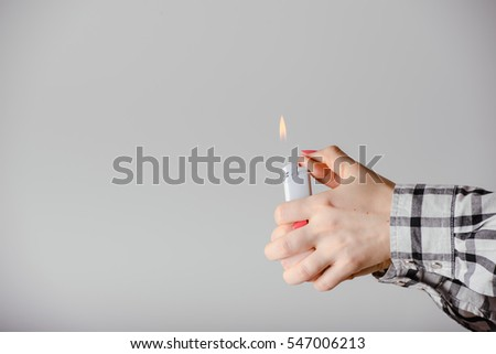 Hand with lighter igniting sparks on light background